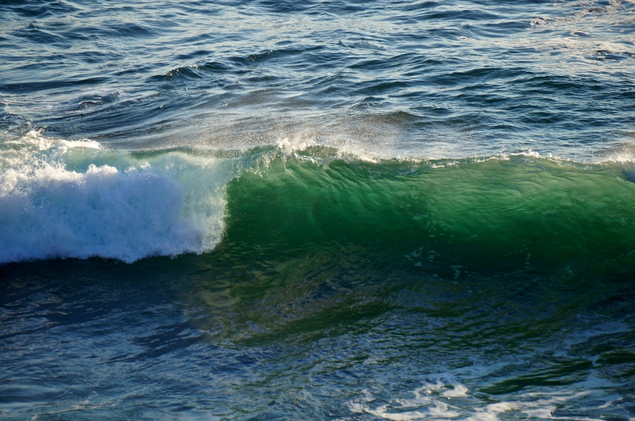 green hue of the the sun in a wave