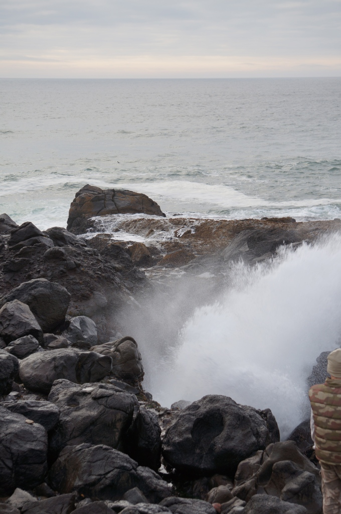 water Kaaa-thumping through a narrow passageway and erupting out a blowhole