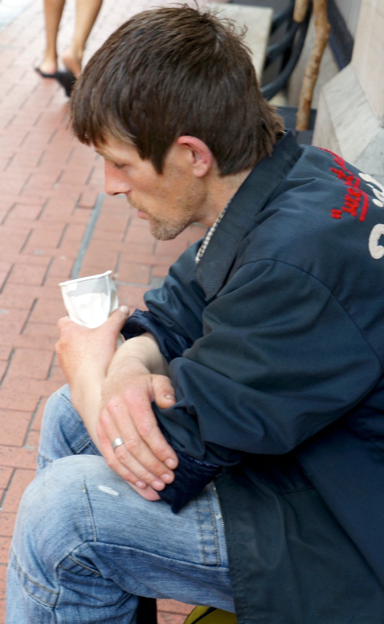 man sleeping as he holds a cup hoping for some change.jpg